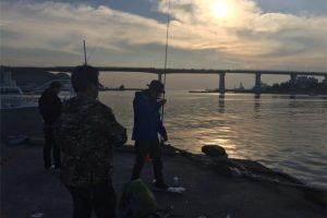 花暮岸壁の朝日と釣り人