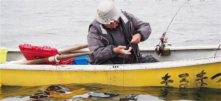 手漕ぎボートで手ビシ釣りをする男性